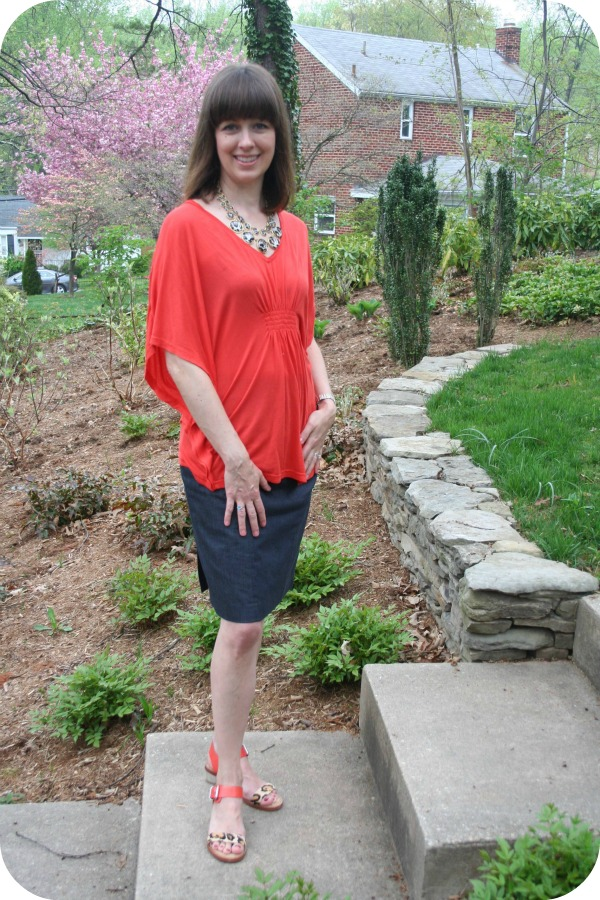 Working mom Casual Friday outfit featuring an orange-red bat-wing blouse, denim pencil skirt, leopard spot necklace, Sam Edelman sandals.